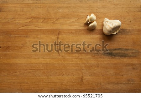 A view looking down on a group of single garlic cloves and a clump of garlic on a worn butcher block cutting board - stock photo