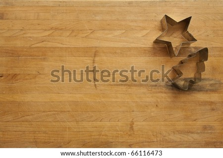 A view looking down on a metal star and tree cookie cutter on a worn butcher block cutting board - stock photo