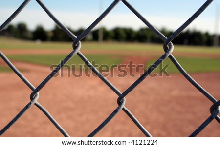 A view of a baseball diamond behind the fench with the chains links in focus. - stock photo