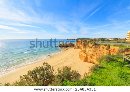 A view of a beach with  a sandy cliff and rocks - stock photo