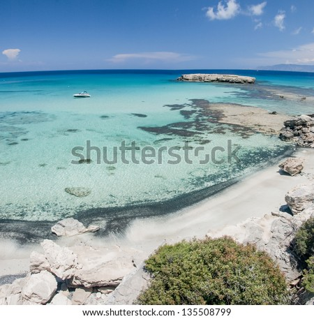 a view of a boat in the sea near a beach, cyprus - stock photo