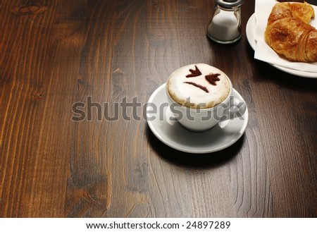 A view of a breakfast table with a cup of cappuccino that has a face showing in the foam - stock photo