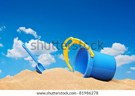 A view of a bucket and scoop at the beach with sky in the background - stock photo