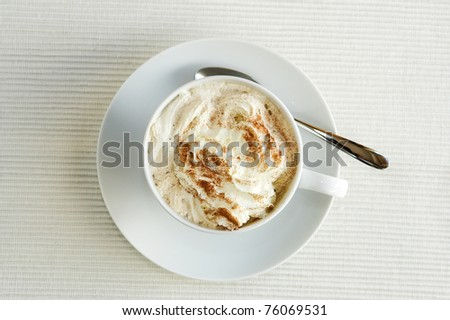 A view of a cappuccino in a white cup, shot from above. The cup is located near a window and shows cream in the cup with sprinkled cocoa on top. - stock photo
