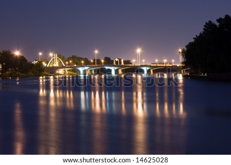 A view of a city bridge with reflections on the river