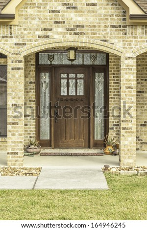 A view of a decorative brown wooden door surrounded by etched glass. - stock photo