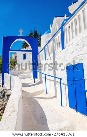 A view of a Greek church with iconic blue and white stairs against clear blue sky on Greek island, Kalymnos, Greece - stock photo