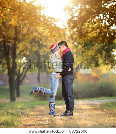 A view of a loving couple kissing in the park in autumn - stock photo