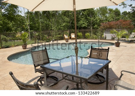 A view of a luxury salt water pool and patio in a residential backyard through patio furniture. - stock photo