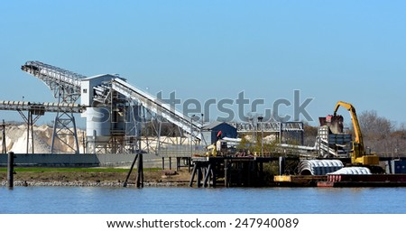 A view of a Mississippi River industrial site with crane moving sand and conveyors in background. - stock photo