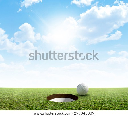 A view of a perfectly manicured golf putting green and hole with a ball on the edge in the daytime on a blue sky background - stock photo