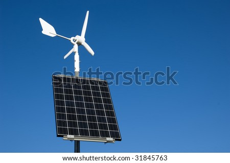A view of a pole with a windmill and solar panels to harness the wind and solar power as alternative energy resources - stock photo