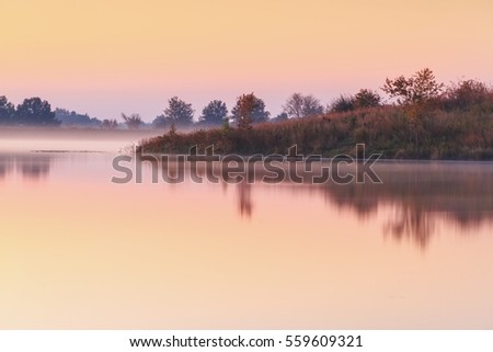 A view of a pond or lake in the autumn.  It is taken during a misty, foggy morning.