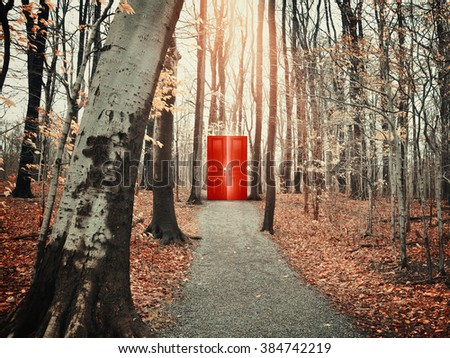 A view of a rocky path trail in the fall forest with bare trees of a glowing red door for a freedom, risk or decision conceptual concept. - stock photo