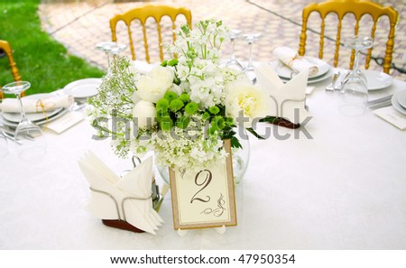 A view of a round banquet table with napkins and silverware set and a colorful flower centerpiece. - stock photo