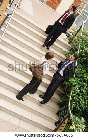 A view of a several people belonging to a business team, standing on the steps of an office building having informal conversation as they leave following an important meeting. - stock photo