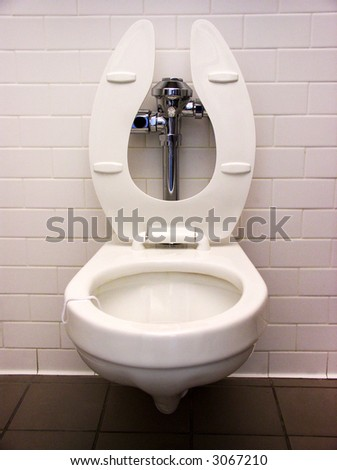 A view of a toilet in a public restroom - stock photo