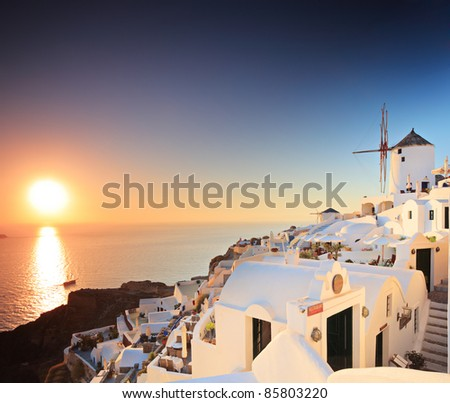 A view of a village on Santorini island, Greece, and a sunset - stock photo