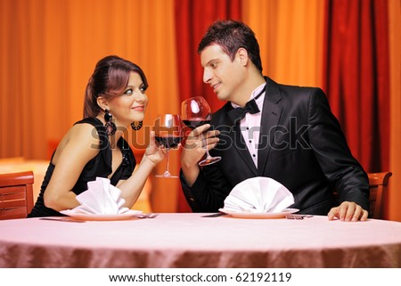 A view of a young couple in love drinking red wine in a restaurant - stock photo