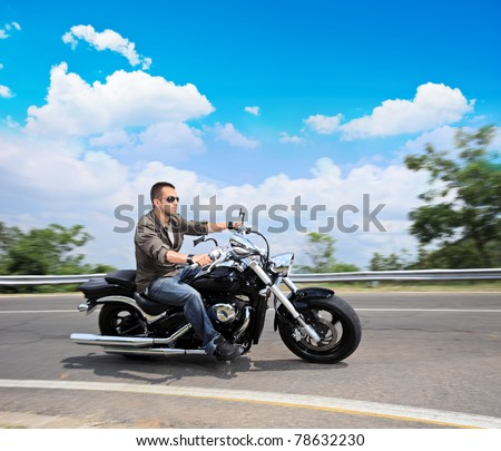A view of a young man riding a motorcycle on an open road - stock photo