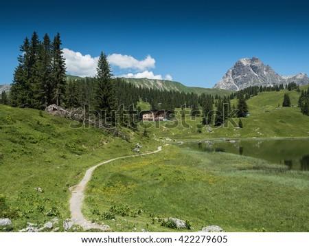 A view of Alpine mountains and the Koerbersee lake near the village Schroecken in Bregenzerwald, region Vorarlberg, Austria - stock photo
