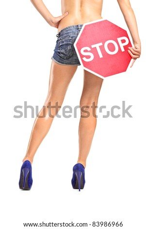 A view of an attractive woman holding a traffic sign stop over her buttock isolated on white background - stock photo