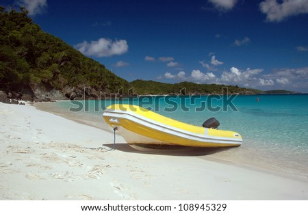 A view of an inflatable dinghy beached on an exotic beach in the Caribbean