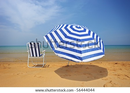 A view of an umbrella and a chair on a sandy beach - stock photo