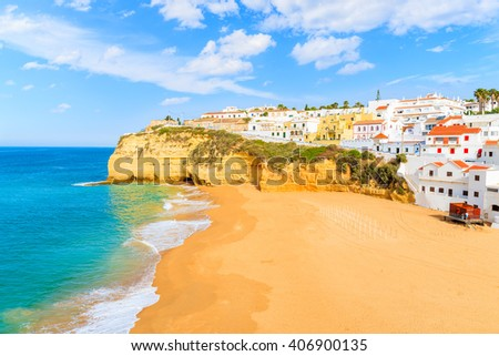 A view of beach with colourful houses in Carvoeiro fishing village, Portugal - stock photo
