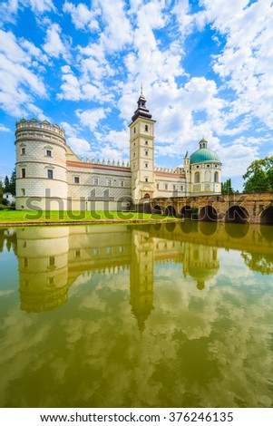 A view of beautiful Krasiczyn castle and its reflection in a lake on a sunny summer day, Poland - stock photo