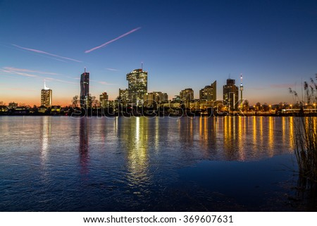 A view of buildings near the Alte Donau in Vienna. Taken in the winter at sunset. Frozen Ice can be seen on the lake. - stock photo
