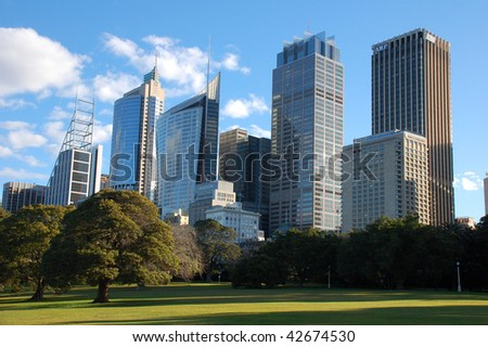 A view of city skyscrapers taken from Royal Botanic Gardens with lawn in foreground - stock photo