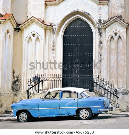 A view of classic american old car parked in front of Havana building facade - stock photo