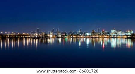 A view of Harrisburg, Pennsylvania's cityscape, state capital, and M. Harvey Taylor Bridge overlooking the Susquehanna River at night. - stock photo