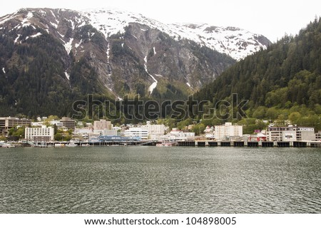 A view of Juneau, Alaska from the sea with Snow capped mountains in the background - stock photo