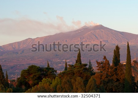 A view of Mt Etna, smoking at sunrise from the Sicilian town of Taormina