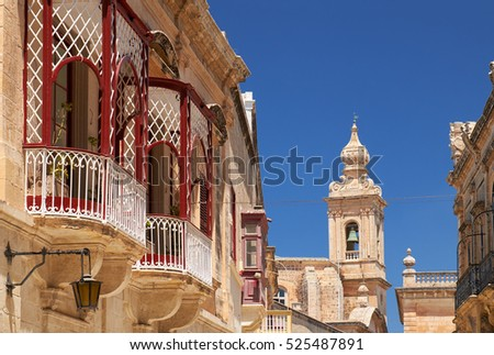 A view of old Mdina street with a traditional Maltese style openwork balconies and Carmelite Church Bell Tower on the background. Malta.