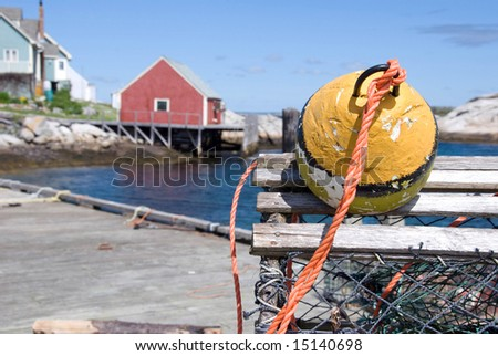 A view of Peggy's Cove in Nova Scotia,Canada with a lobster trap and float marking the foreground. - stock photo