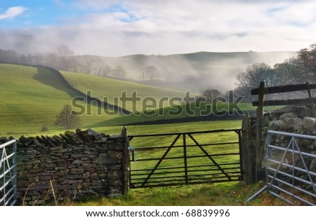 A view of rolling English Countryside near Staveley, Cumbria. Mist i the distance, and a gate and dry-stone wall in the foreground - stock photo