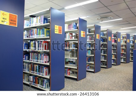 A view of rows of bookshelves and a study area inside a library. - stock photo