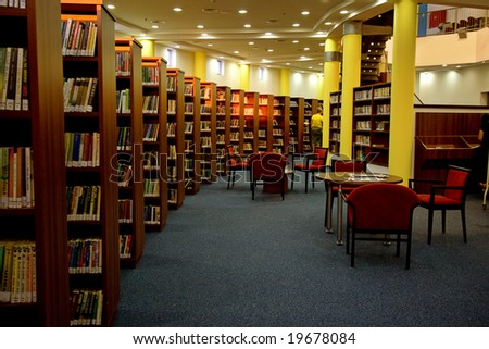 A view of rows of bookshelves and a study area inside a modern library. - stock photo