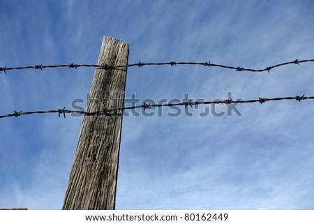 Barbed wire on fence post Stock Photos, Illustrations, and Vector Art