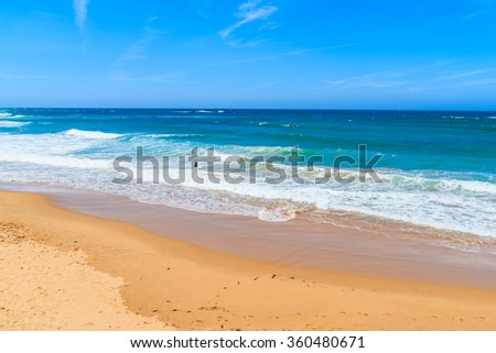 A view of sandy Praia do Amado beach with surfers in sea, Portugal