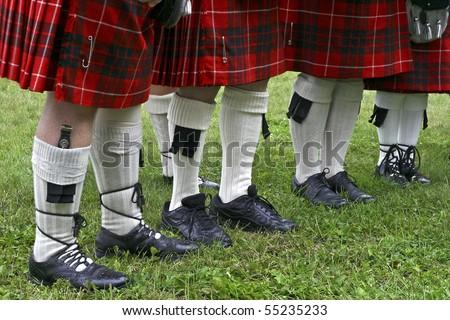 A view of Scottish tartan kilts and stockings with dress shoes and Skean Dhu boot knife tucked into calf length stockings. - stock photo