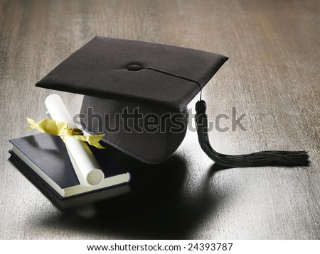 A view of several items related to education and graduation including a graduation cap with tassel, a book and a rolled up diploma - stock photo