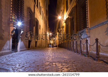 A view of sides streets and pedestrian paths between buildings in central Rome at night - stock photo