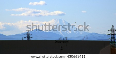 A view of snow capped Mount Fuji on the horizon with two kites flying in the foreground, as well as some power lines.  Taken in Saitama prefecture, Japan. - stock photo
