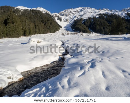 A view of snow - covered landscape  with stream  from the trail of Klosters - stock photo