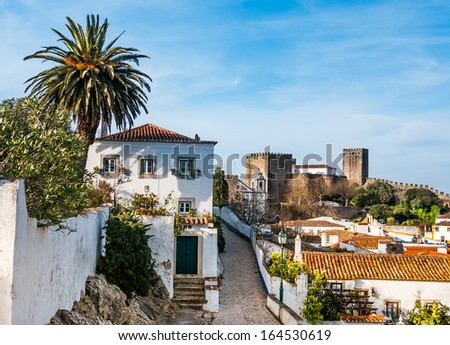 A view of streets and the fortified wall in Obidos, Portugal. The name Obidos probably derives from the Latin term oppidum, meaning citadel, or fortified city - stock photo