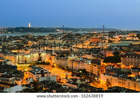 A view of the Alfama downtown and the 25 de Abril Bridge in Lisbon, Portugal - stock photo
